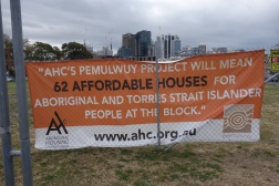 Banner for the Aboriginal Housing Corporation's Pemulwuy Project on the fenced area of the Block